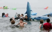 Youngsters take to the water with inflatable sharks as they attend the Jaws Fest 2005 celebrating the release of the 30th anniversary edition DVD of the film 'Jaws' at Martha's Vineyard, Massachusetts June 4, 2005.  Photo by Reuters (Handout)